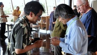 Dr. Sato exchanging cards with a federation member.